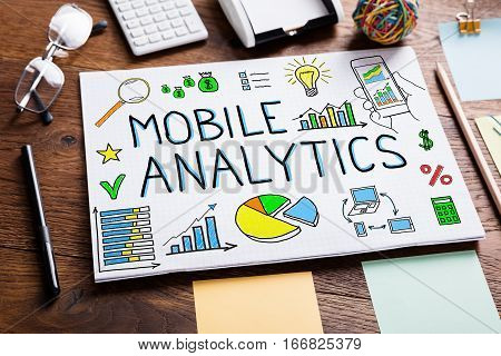 High Angle View Of Illustrative Diagram Of Mobile Analytics Concept On White Paper On Wooden Desk In Office
