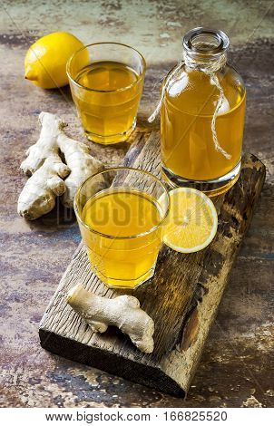 Homemade fermented raw ginger lemon kombucha tea. Healthy natural probiotic flavored drink.