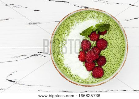 Matcha green tea chia seed pudding bowl vegan dessert with raspberry and coconut milk. Overhead top view flat lay copy space