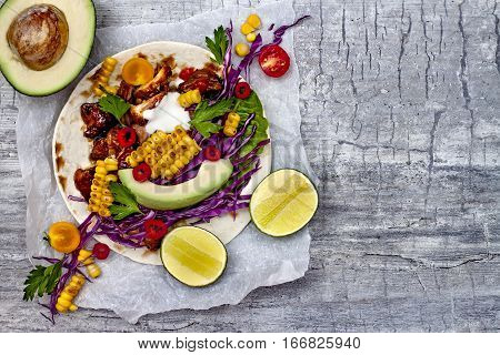 Mexican tacos with avocado slow cooked meat grilled corn red cabbage slaw and chili salsa on rustic stone table. Recipe for Cinco de Mayo party. Top view. Copy space background