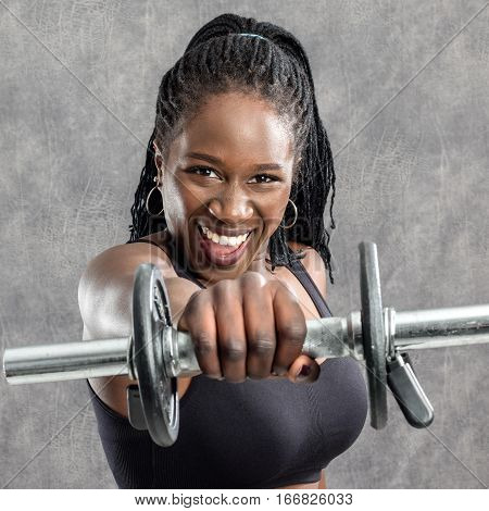 Close up portrait of sportive black teen with braids holding dumbbell in front of face. Young woman in sportswear with vigorous face expression against grey background.