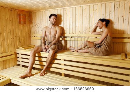 Attractive young couple relaxing in sauna at the spa