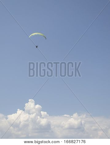 Flying parachute, high in the clouds on blue sky