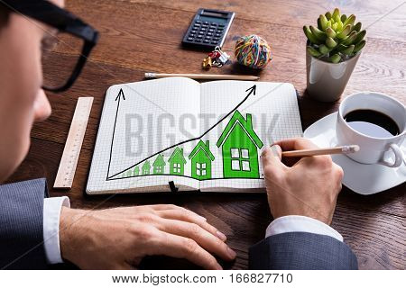 Close-up Of Businessman Drawing Growth In Real Estate Prices In Notebook On Wooden Desk