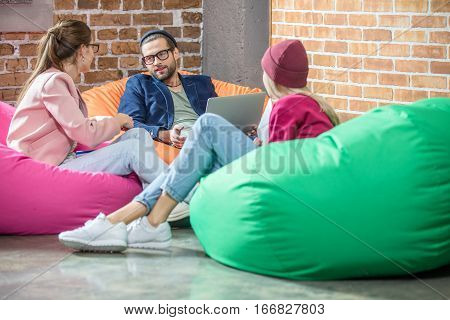 Young people sitting in bean bag chairs and chatting