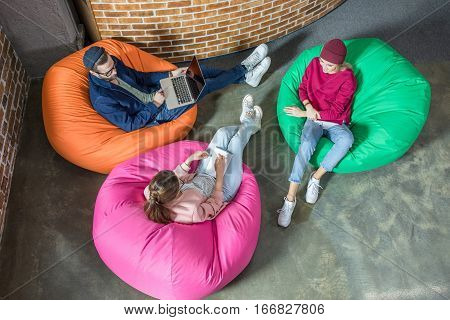Top view of young stylish people chatting while sitting in bean bag chairs