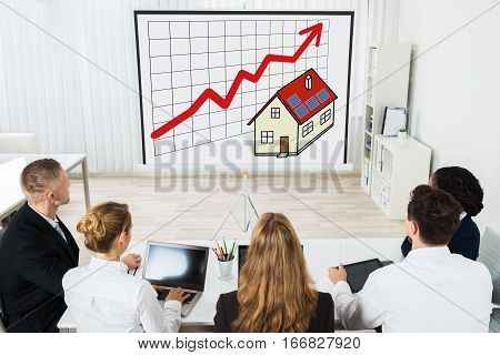 Business People Team Sitting In A Meeting Looking At Projector Screen With Property Growth Diagram