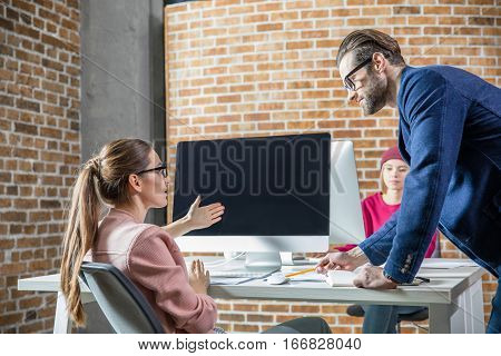 Young man and woman discussing something in modern office