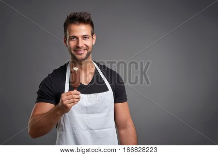 A handsome young barista man smiling and enjoying an ice-cream
