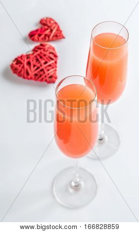 Two bellini cocktails with hearts on the white background