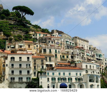 Old Italian town on a mountain. Amalfi terrace houses view. White stone buidings in south Italy. Positano region town from coastline. Red roofs and white walls of italian homes. Travel in Italy