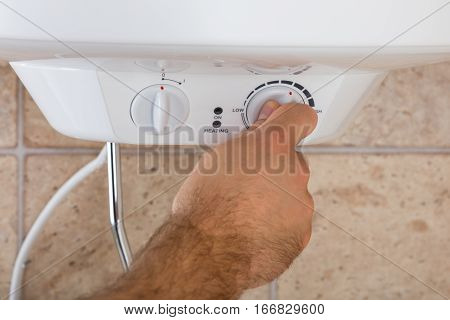 Close-up Of Man's Hands Turning The Knob Of Electric Boiler