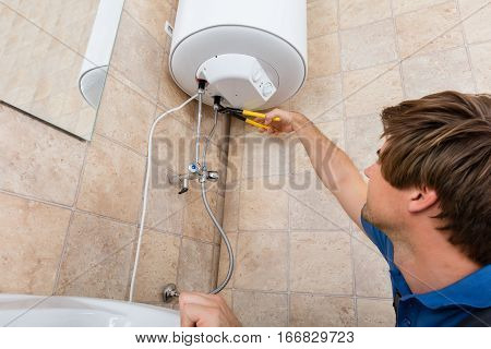 Low Angle View Of Technician Repairing Electric Boiler At Home