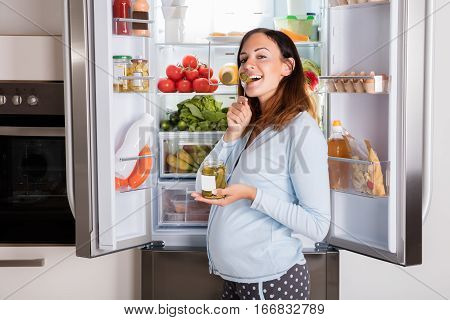 Young Pregnant Woman Enjoy Eating Jar Of Pickle In Front Of Open Refrigerator In Kitchen