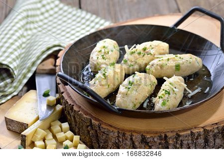 Traditional South Tyrolean cheese dumplings (so-called 'Kasnocken') made of white bread and hearty mountain cheese, served with melted butter, grated parmesan and chives
