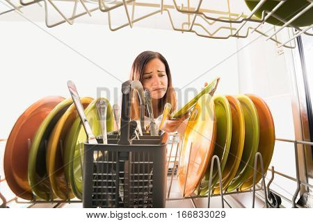 Young Unhappy Woman Looking At Unclean Plate Near Dishwasher In Kitchen