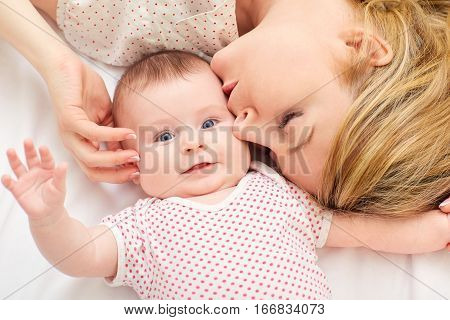 Mum kisses baby on the bed in room.