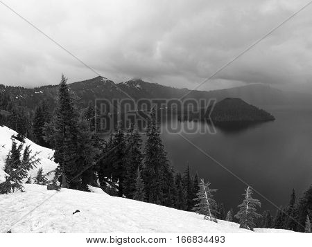 Rain rolls in to Crater Lake National Park over Wizard Island within the deep water with fir trees and lots of snow remaining on a spring day.