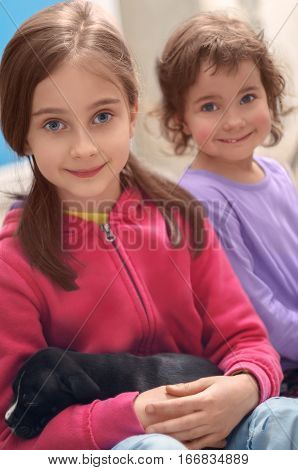 Home portrait of two cute smiling little girls with sleeping puppy on hands of Staffordshire Terrier dog
