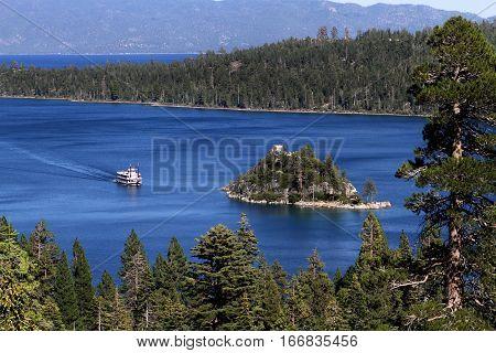 Paddle boat cruises toward Fannette Island on Lake Tahoe in California USA.
