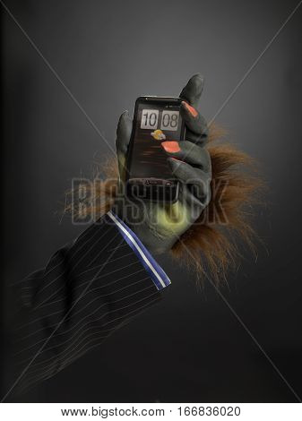 Hairy hand holding cell phone against gray graduated background