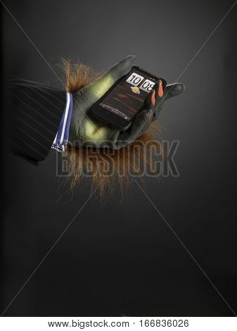 Hairy hand holding cell phone against grey graduated background