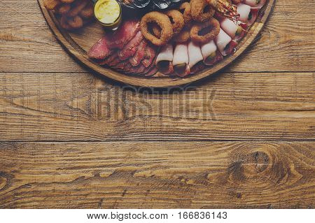 Seafood and meat platter board on wood background with copy space. Mediterranean cuisine restaurant food, fried calamari rings, mussels, prosciutto delicacy. Catering, banquet table, menu mockup