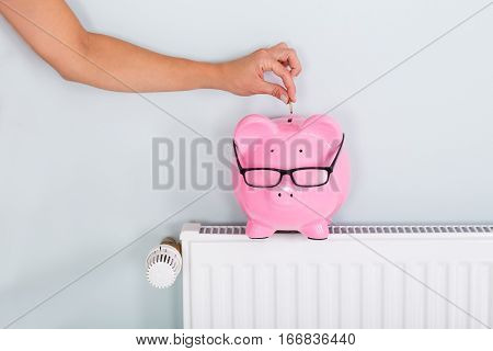 Woman Hand Inserting Coin In Piggy Bank On Radiator To Save On Energy Bill