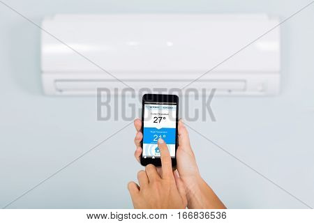 Woman Hand Setting Temperature Of Air Conditioner Using Smartphone App At Home
