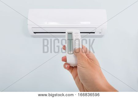 Close-up Of A Person Hand Operating Air Conditioner With Remote Control At Home
