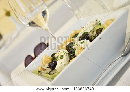 Tilted view of a Mediterranean salad with cheese crisps and olives in a restaurant