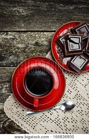 Coffee red cup pieces of chocolate on the wooden table background. Tinted. Top view.