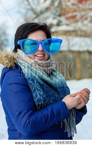 European brunette girl in big clown glasses with scarf, smiling, standing outdoor rubbing his hands in cold winter