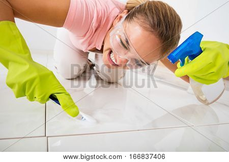 Young Stressed Woman Removing Stain On The Floor With Brush And Spray Bottle At Home