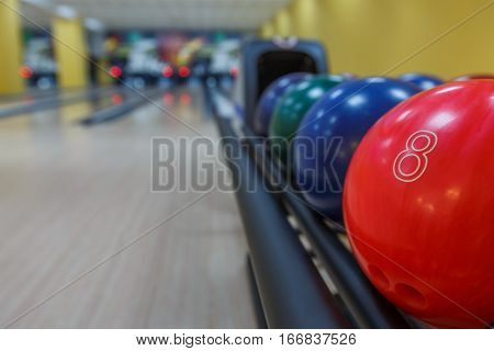 Bowling background. Interior of bowling alley lane with balls return machine closeup, selective focus on red ball