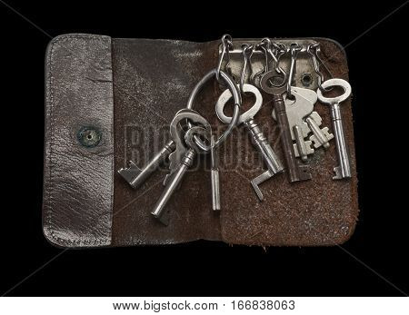 Old keys in key in leather key wallet on Black background