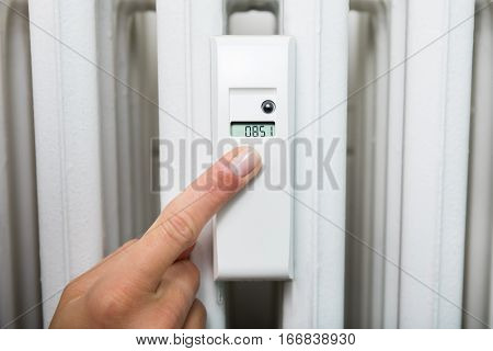 Close-up Of Woman Taking Heating Consumption Reading From Digital Thermostat