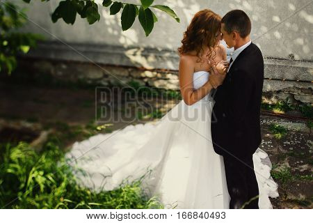 Fiance Holds Delicate Bride's Arms Near His Heart Standing In The Garden