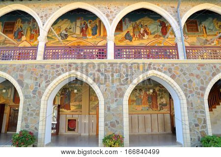 TROODOS MOUNTAINS, CYPRUS - NOVEMBER 18, 2015: The arcades inside Kykkos Monastery with colorful mosaics