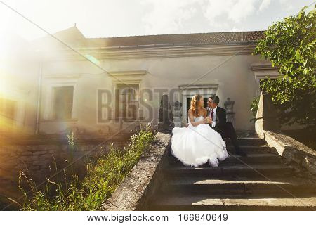 Sun Shines Under A Wedding Couple Sitting On The Old Stone Footsteps