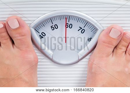 Close-up Of Person Feet Standing On Weighing Scale