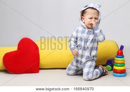 Portrait of unhappy little baby boy sitting with toys and crying.