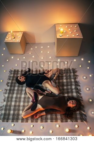 Two Young Women Relax Doing Yoga Asana Lotus Lying On Plaid In Cozy Room With Candles