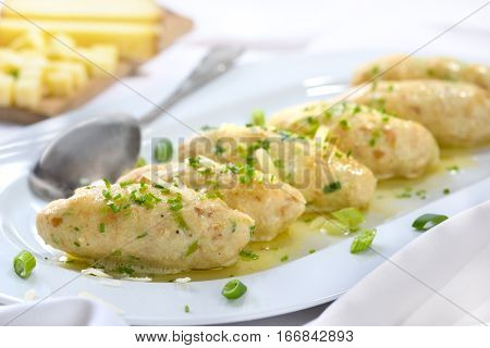 Traditional South Tyrolean cheese dumplings (so-called 'Kasnocken') made of white bread and hearty mountain cheese, served with melted butter, grated parmesan and chives on a white platter