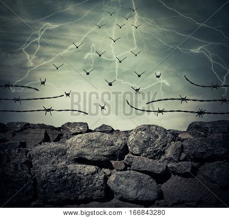 Stone wall fence of a prison with barbed metallic wire on top transform into flying birds over the lightning sky background. Freedom and success concept.
