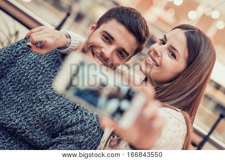 A happy couple having fun and taking a selfie.They are enjoying city life.