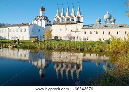 The bell tower and the Intercession church with the reflection in the monastery pond. October evening in the Tikhvin assumption monastery. Russia
