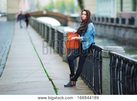 beautiful girl in blue jeans jacket and scarf straightens hair standing near the parapet on the embankment. In her hand brown elegant handbag