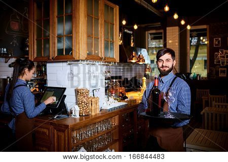 The waiter, sommelier, bartender with  beard carrying a tray  wine glasses in the bar.