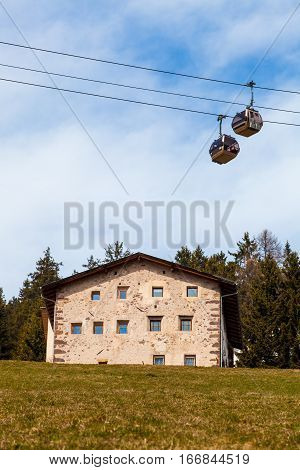 House on the hill and mountain gondola lift. Passenger cabin lift and house on a green hill in mountain. Blu sky background. Some trees in the woods. Location, Ortisei, Northern Italy